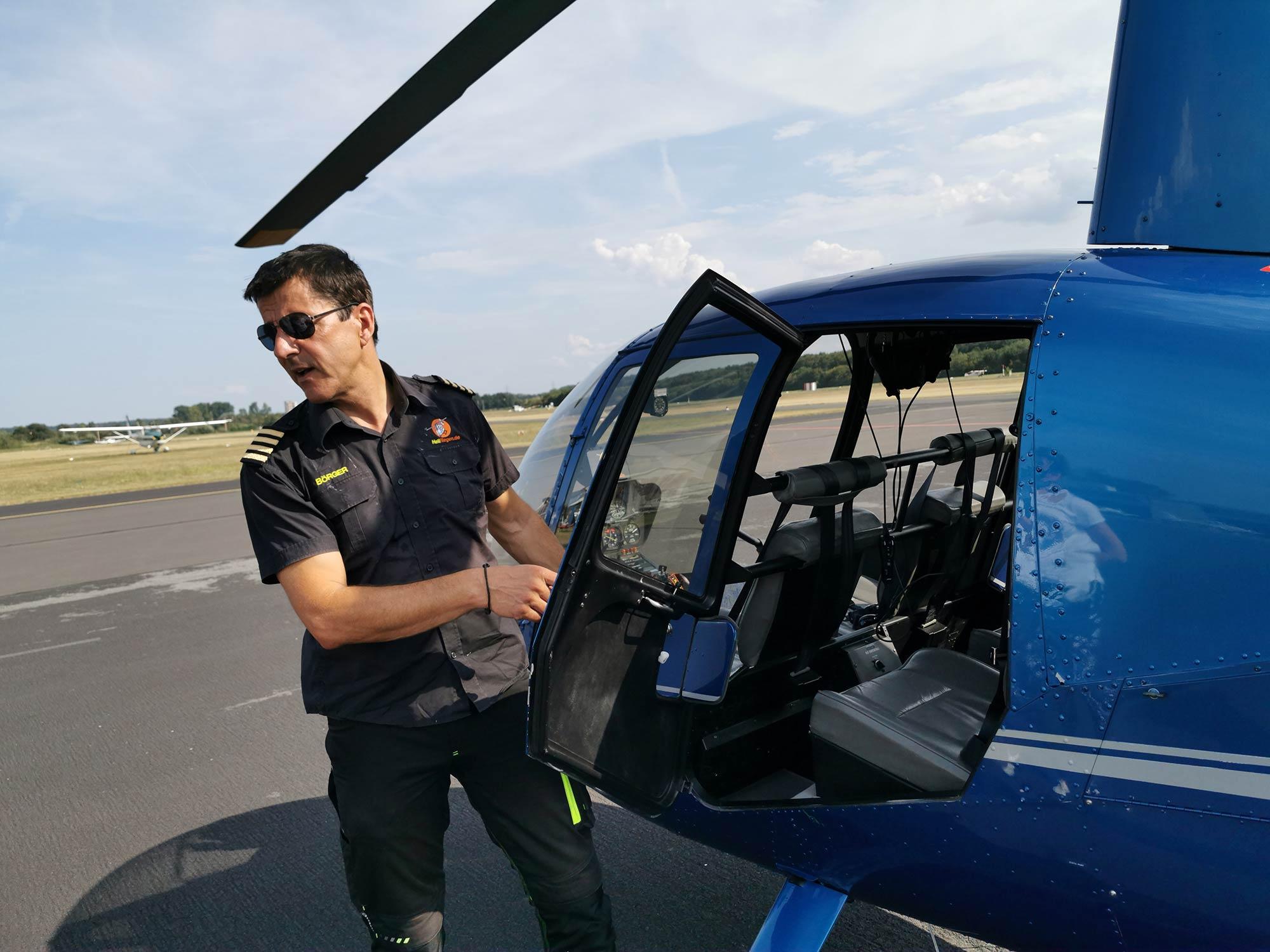 Flying helicopter over Frankfurt using Helifliegen - Pilot opening door of helicopter
